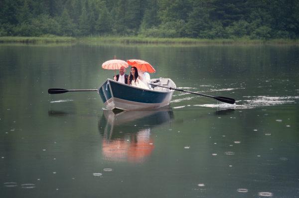Novia llegando en barca bajo la lluvia